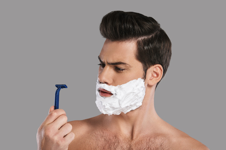 Bad razor? Confused young man with foam all over his face looking at razor while standing against grey background Banque d'images
