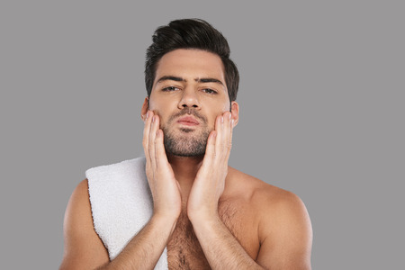 Taking care of his skin. Handsome young man looking at camera and touching his face while standing against grey background