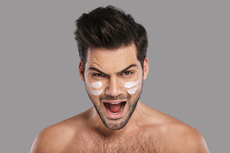 What?! Handsome young man applying moisturizer and screaming while standing against grey background Banque d'images