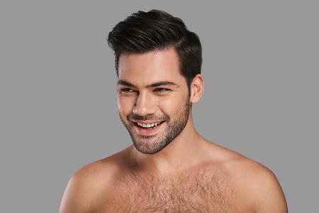 新鮮でハンサム。灰色の背景に立ちながら遠ざかるハンサムな若い笑顔の男 写真素材