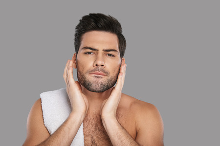 His skin needs good care. Handsome young man looking at camera and touching his face while standing against grey background Stock fotó
