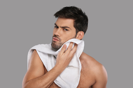 Everyday routine. Handsome young man wiping his face with towel while standing against grey background Banque d'images