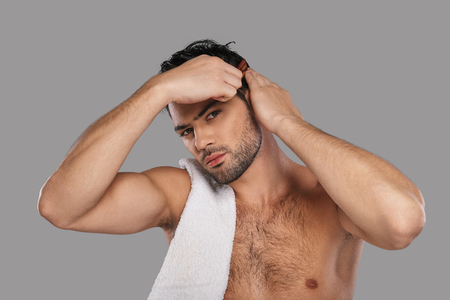 Perfect man. Good looking young man combing his hair while standing against grey background
