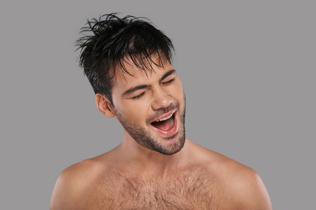 Feeling free to do anything. Good looking young man keeping mouth open and eyes closed while standing against grey background