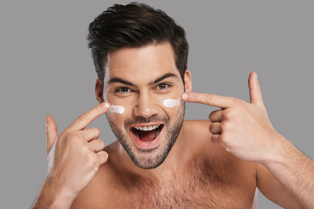 Amazing results! Handsome young smiling man applying moisturizer and looking at camera while standing against grey background