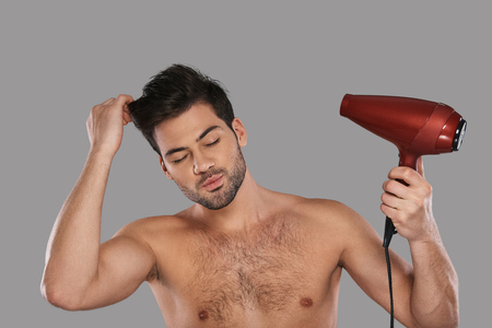 Beauty treatment. Handsome young man drying his hair while standing against grey background