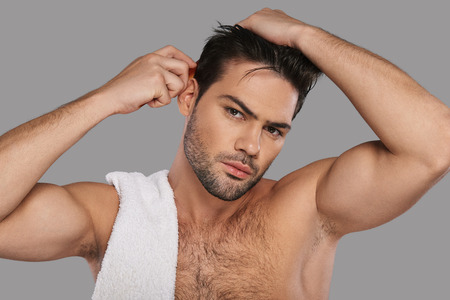 Everything must be perfect. Good looking young man combing his hair while standing against grey background