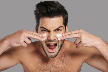 Dealing with everything like a man. Handsome young man applying moisturizer and screaming while standing against grey background