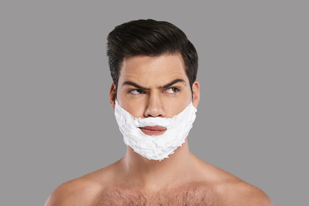 Ready to shave. Confused young man with foam all over his face looking away while standing against grey background
