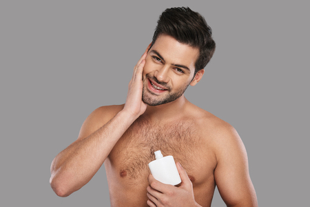 Feeling so fresh. Handsome young man applying aftershave lotion and smiling while standing against grey background Banque d'images