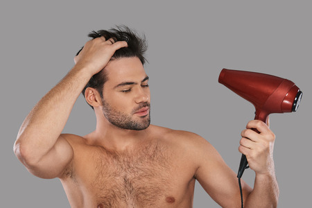 Used to look perfect. Handsome young man drying his hair and keeping eyes closed while standing against grey background