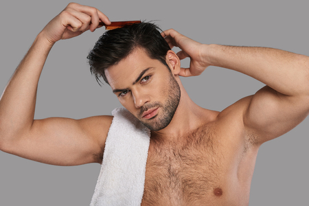Everything should be perfect. Good looking young man combing his hair while standing against grey background