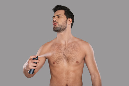 Feels good! Handsome young man looking away and applying deodorant while standing against grey background