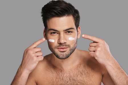 Taking care of his skin. Handsome young smiling man applying moisturizer and looking at camera while standing against grey background Banque d'images