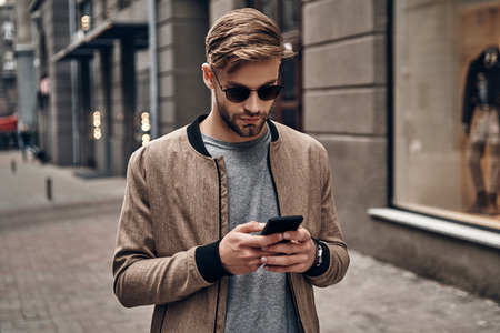 Surfing the net. Handsome young man in casual wear using his smart phone while standing outdoors