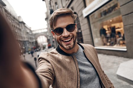 Positively charming. Self portrait of handsome young man in casual wear smiling while standing outdoors Imagens - 91959498