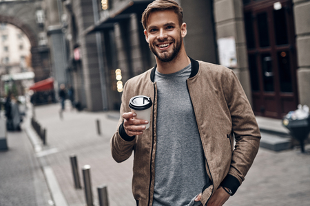 Enjoying coffee outdoors. Handsome young man in casual wear holding disposable cup and smiling while walking through the city street Imagens