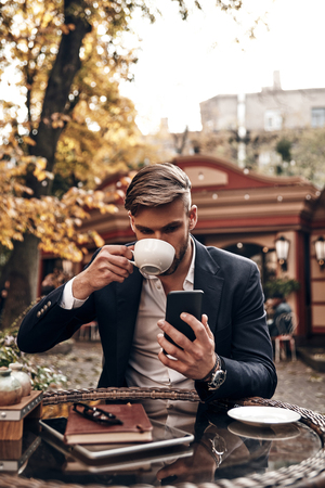 Coffee during working day. Handsome young man in smart casual wear drinking coffee and looking at his smart phone while sitting in cafe outdoors