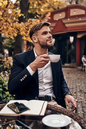 Taking a moment to enjoy the day. Handsome young smiling man in smart casual wear holding a cup of coffee and looking away with smile while sitting in restaurant outdoors Imagens