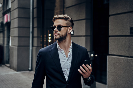 Confidence and style. Handsome young man in smart casual wear holding his smart phone while standing outdoors