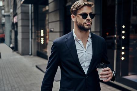 Perfekter Geschäftsmann . Hübscher junger Mann in der intelligenten Freizeitkleidung , die Einwegbecher trägt , während der Stadt durch die Stadtstraße geht