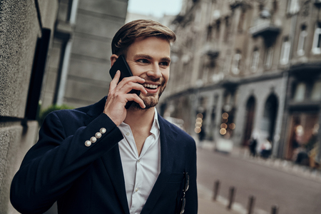Feeling happy. Handsome young man in smart casual wear talking on the phone while walking through the city street Imagens