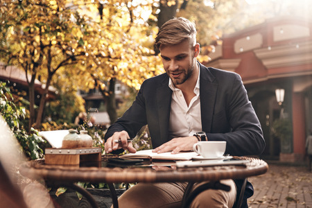 Planning the day. Good looking young smiling man in smart casual wear checking out his notes in personal organizer while sitting in restaurant outdoors