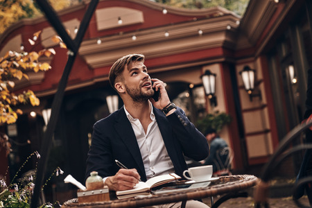 Listening to clients requirements. Handsome young man in smart casual wear talking on his smart phone and writing something down while sitting in restaurant outdoors Imagens - 91959588