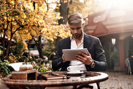 Always online. Good looking young man in smart casual wear using digital tablet while sitting in restaurant outdoors