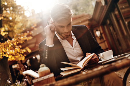 This is going to be a long day. Good looking young man in smart casual wear holding his personal organizer and looking at it while sitting in restaurant outdoors