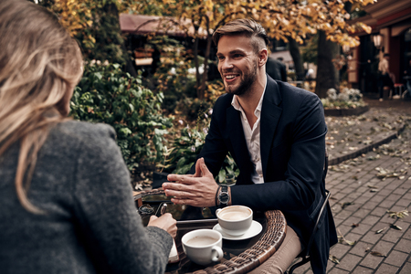 Sharing great ideas. Handsome young man in smart casual wear smiling while having a conversation with young woman in restaurant outdoors