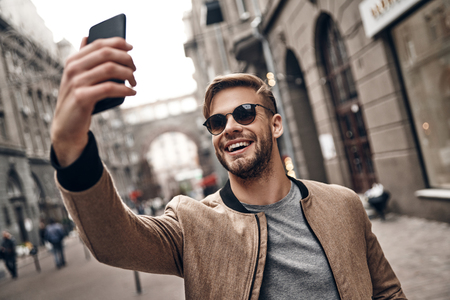 Sharing happy selfie. Handsome young smiling man in casual wear taking selfie using his smart phone while standing outdoors Imagens - 91959594