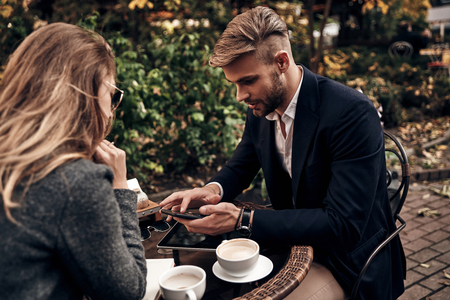Using technologies in business.  Handsome young man in smart casual wear using his smart phone while having a conversation with young woman in restaurant outdoors Imagens - 91959595