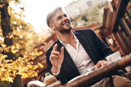 His business is his life. Good looking young man in smart casual wear smiling and looking away while sitting in restaurant outdoors
