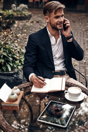 I can totally make it work! Top view of handsome young smiling man in smart casual wear talking on his smart phone and writing something down while sitting in restaurant outdoors