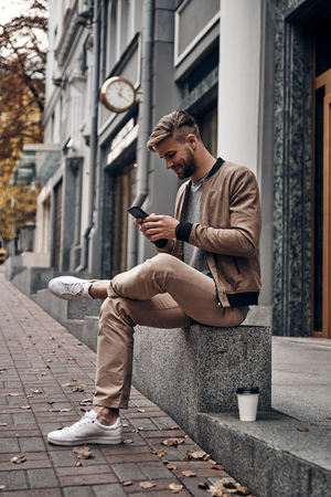 Always online. Handsome young man in casual wear using his smart phone while sitting outdoors Imagens - 91959598