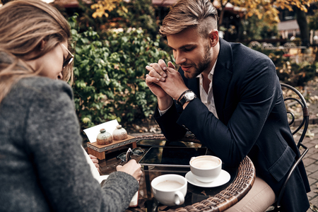 Good business talk. Handsome young man in smart casual wear smiling while having a conversation with young woman in restaurant Imagens - 91959599