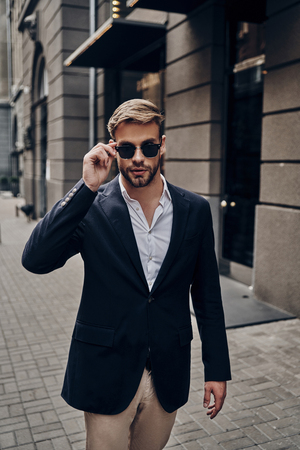 In his own style. Handsome young man in smart casual wear adjusting his eyewear while walking through the city street Imagens