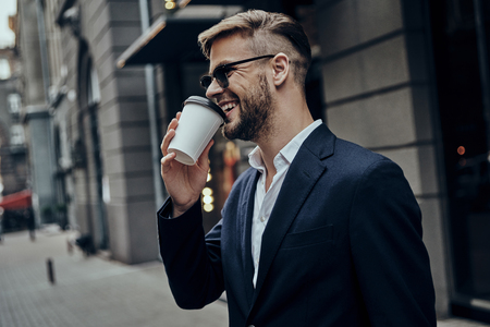 Simply happy. Handsome young man in smart casual wear drinking coffee and smiling while standing outdoors