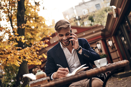 Discussing business details. Good looking young man in smart casual wear talking on his smart phone and smiling while sitting in restaurant outdoors Imagens