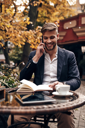 I am waiting for you! Good looking young man in smart casual wear talking on his smart phone and smiling while sitting in restaurant outdoors