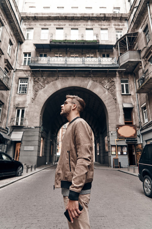 Feeling the city. Handsome young man in casual wear carrying his smart phone and looking away while standing outdoors Imagens