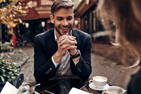 Job interview. Handsome young man in smart casual wear smiling while having a conversation with young woman in restaurant
