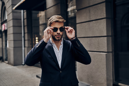 His style is perfect. Handsome young man in smart casual wear adjusting his eyewear while walking through the city street