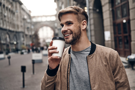Enjoying fresh coffee. Handsome young man in casual wear holding disposable cup and smiling while walking through the city street Imagens - 91959916