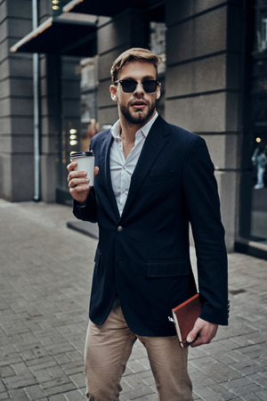 Always in a hurry. Handsome young man in smart casual wear carrying disposable cup while walking through the city street