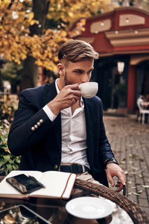 Enjoying fresh coffee. Handsome young man in smart casual wear drinking coffee while sitting in restaurant outdoors Imagens - 91959918