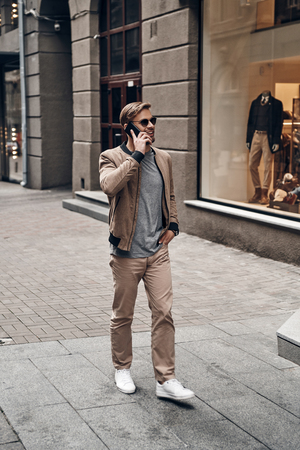 Amazing day in the city. Full length of handsome young man in casual wear talking on his smart phone and smiling while walking through the city street Imagens