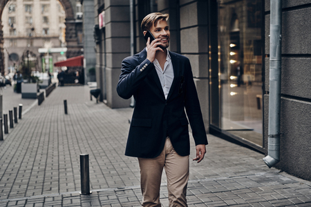On the way to business meeting. Good looking young man in smart casual wear talking on his smart phone and smiling while walking through the city street Imagens