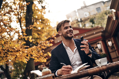 Busy working day. Good looking young man in smart casual wear holding his smart phone and smiling while sitting in restaurant outdoors